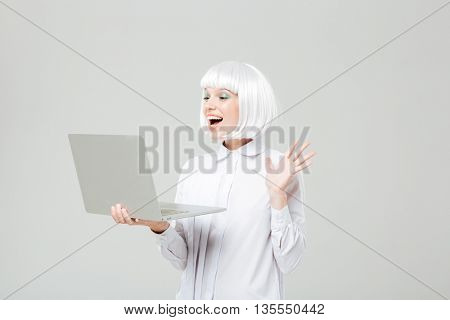 Cheerful lovely young woman standing and using laptop