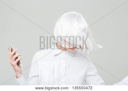 Attractive young woman with blonde hair listening to music from cell phone and dacing