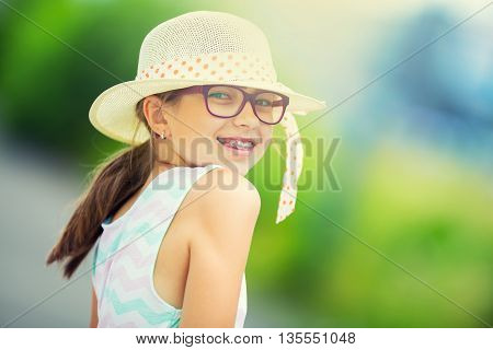 Girl.Happy girl teen pre teen. Girl with glasses. Girl with teeth braces. Young cute caucasian blond girl in summer outfit.