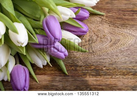 bouquet of white and purple tulips on wood