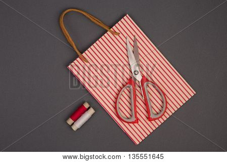 Grey And Red Thread, Scissors And Gift Pack On Grey Background