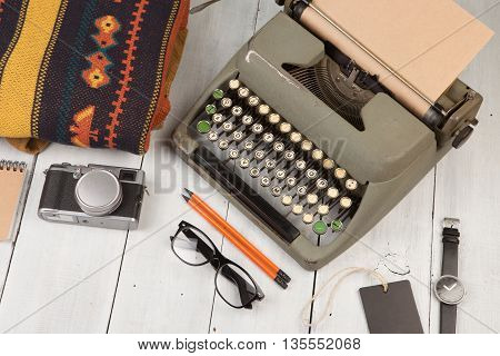 Typewriter, Notepad, Camera, Clothes, Glasses And Watch On Wooden Background
