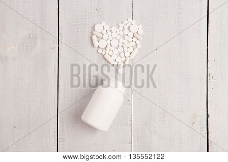 Medical concept - white heart of pills and capsules on white wooden desk