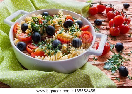 Pasta (fusilli) in white pan on wooden background. Vegeterian cooked with tomatoes black olives garlic and parsley.