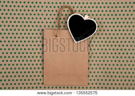 Shopping Bag And Blank Blackboard In The Form Of Heart On Craft  Paper Background In Green Polka Dot
