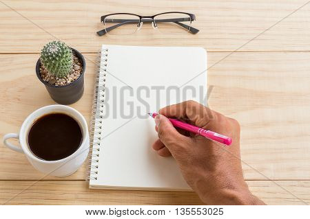Vintage office desk table with notebooks pen and a cactus with cup of coffee. Top view with copy space. Hand holding pen on notebook. Business concept