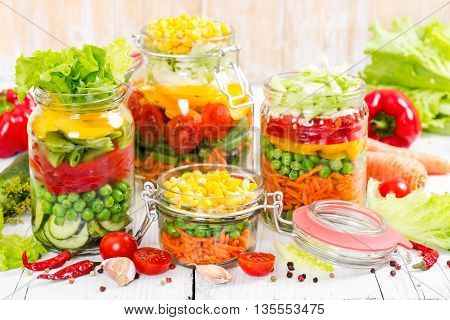 Prepared For Canning Colorful Vegetables In Glass Jars On Wooden Background.