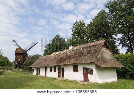 Brede, Denmark - June 23, 2016: Ancient danish farmhouse and windmill in Frilandsmuseet.