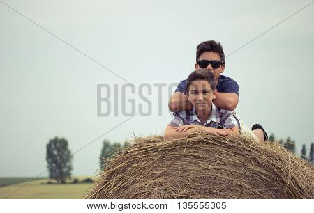 a haystack backs to each other. children in a field