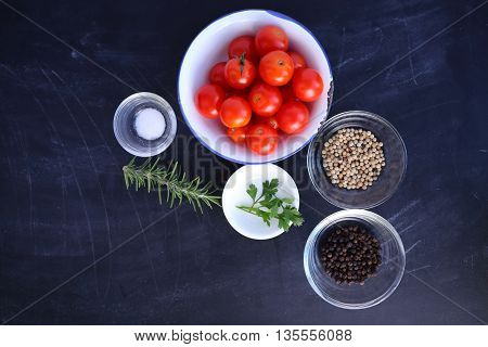 Cherry tomatoes pepper parsley rosemary and salt on black background