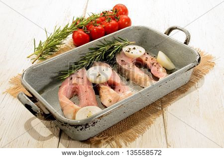 fresh carp steaks with onion rings and rosemary in an old roasting tin