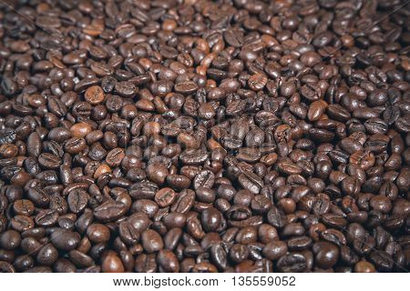 Heap of black coffee beans, brown food background, copy space, selective focus