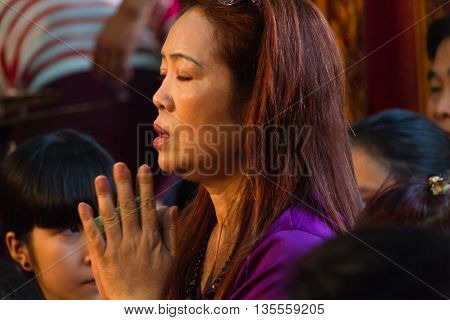 Thanh Hoa, Vietnam - October 19, 2014: A woman prays during a Dao Mau ceremony (spirit mediumship) with tears in her eyes in Central Vietnam.