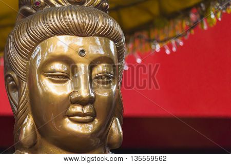 Thanh Hoa, Vietnam - October 19, 2014: The face of a statue of Guanyin, the spiritual figure of mercy and mother goddesses, in front of a temple.