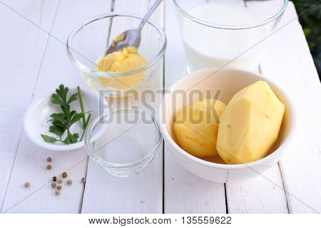Ingredients for mashed potatoes on white wooden