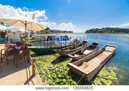 Shuanglang, China - October 6, 2014: View across lake Erhai in Yunnan province with small boats on a sunny day.