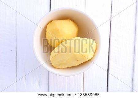 peel potato in bowl on white wooden