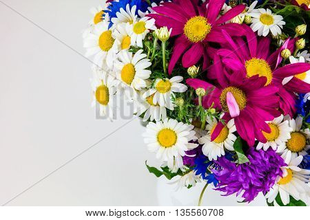 Romantic composition with bouquet of wildflowers on white background with copy space. Floral decor. Concept for greeting card. Beautiful bouquet of bright wildflowers. Bouquet of summer wildflowers.