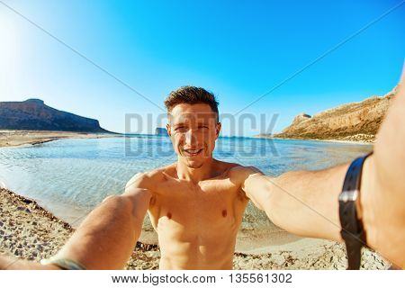 man is sunbathing on the sand on the beach. Male partially in water, taking selfie