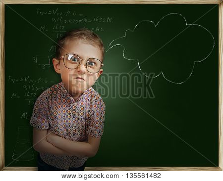 Emotional pupil boy near school chalkboard .