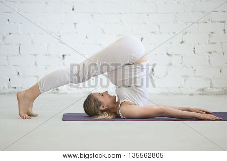 Pregnant Young Woman Doing Prenatal Yoga. Plow Pose