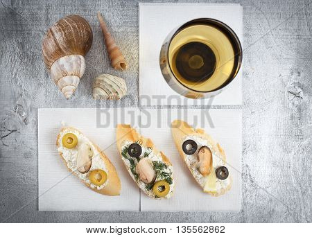 Tasty various italian sandwiches with seafood against rustic wooden background. Crostini with cheese mussels and sliced olives horizontal top view