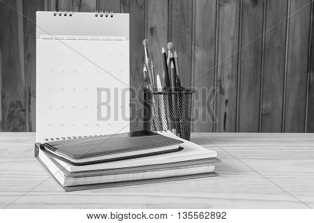 Black and white Note bookpenpencil and stack of book with calendar on wooden table background