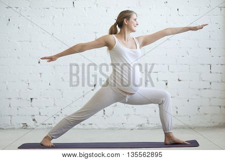 Pregnant Young Woman Doing Prenatal Yoga. Warrior Two Pose