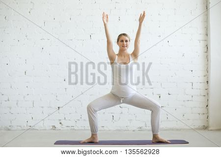 Pregnant Young Woman Doing Prenatal Yoga. Sumo Squat Pose