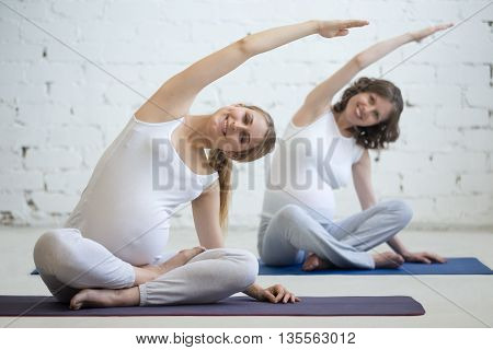 Pregnant Young Women Doing Prenatal Yoga. Bending In Easy Pose