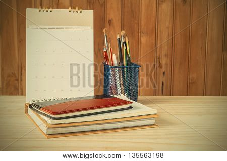 Note bookpenpencil and stack of book with calendar on wooden table background.vintage tone