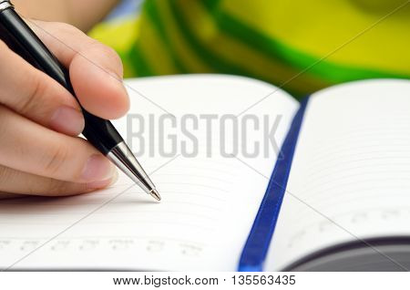 Write activity (A girl hand holds a pen and write on a blank book) with selective focus