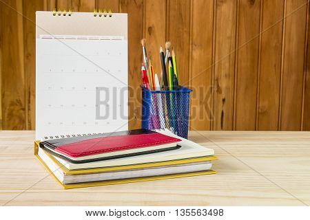 Note bookpenpencil and stack of book with calendar on wooden table background