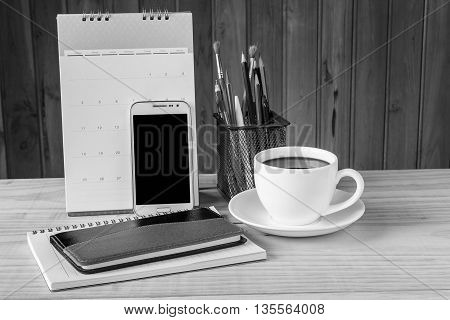 Note book smart phone coffee cup and stack of book with calendar on wooden table background. Black and white tone
