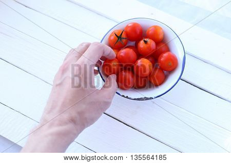 Hand pick cherry tomatoes on white wooden background