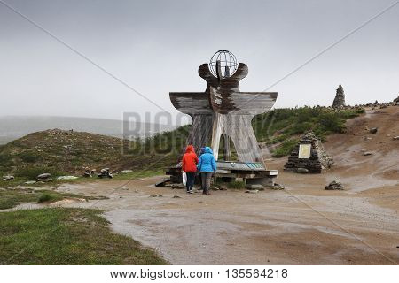 ARCTIC CIRCLE NORWAY - JULY 30 2015: People visit statue at Arctic Circle Norway. Foreign tourists spent some 5 million overnight stays in Norway in 2013.