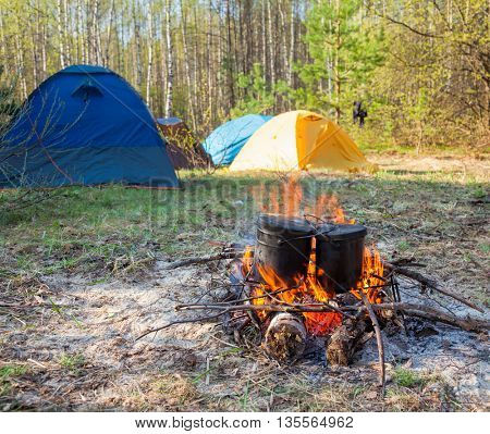 Cauldrons over burning campfire with camping tent in background