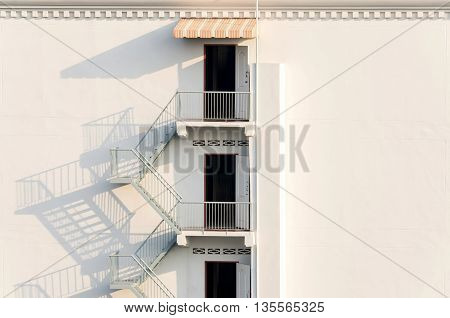 Fire Escape With Afternoon Shadows On Exterior Wall.