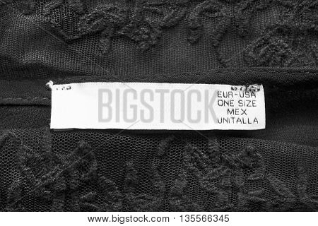White clothes label on black lace as a background