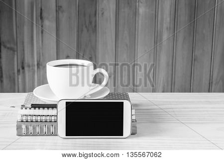 Note booksmart phonecoffee cupand stack of book on wooden table background. black and white tone