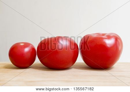 Three fresh tomatoes lined up by size
