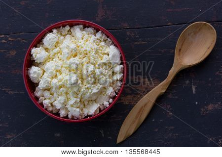 red plate with white milky curd and juniper wooden spoon on an old black wooden table. top view close-up