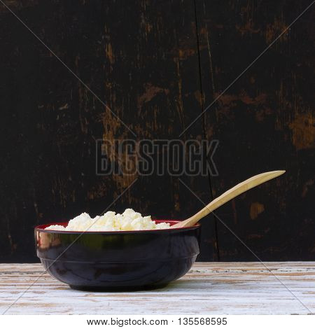 black plate with yellow fresh cheese and juniper spoon on white wooden table. side view close-up. selective focus. square photo