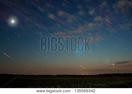 Abstract gentle background with clouds and stars in the form of tracks over fields and forests