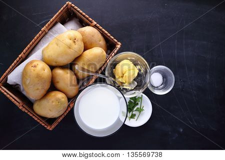 ingredients for mashed potatoes on black background