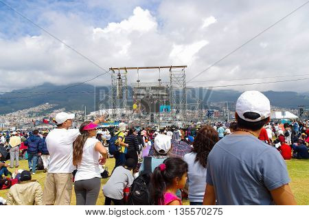 QUITO, ECUADOR - JULY 7, 2015: People very far from the scaffold looking and attending to mass on big screen.