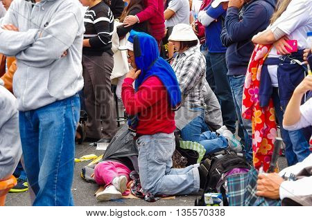QUITO, ECUADOR - JULY 7, 2015: People on knees in the middle of the mass, praying. Family on the floor.
