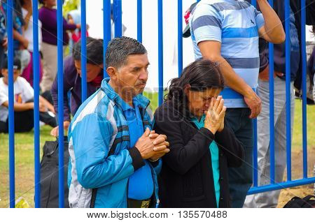 QUITO, ECUADOR - JULY 7, 2015: A couple of adults praying in poep Francisco mass, join hands and down head.
