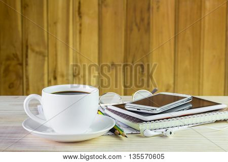 Note booksmart phonecoffee cupand stack of book on wooden table background
