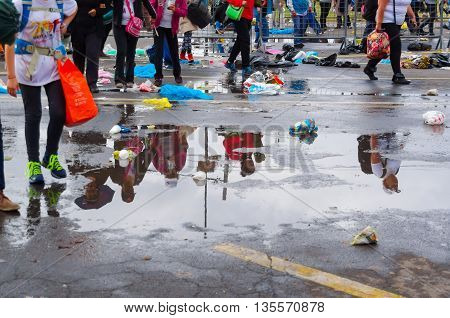 QUITO, ECUADOR - JULY 7, 2015: After raining water puddle stay on the street, people shadows on them, and walking on the sides.